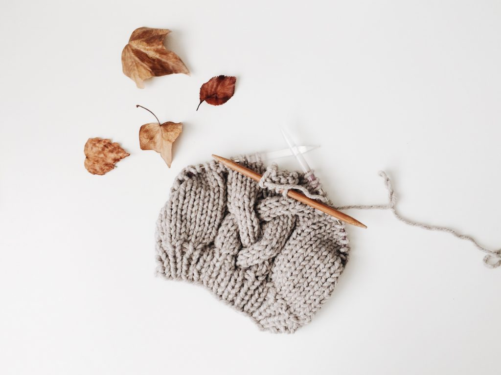 Unfinished knitting project - a half knitted beanie hat in taupe yarn