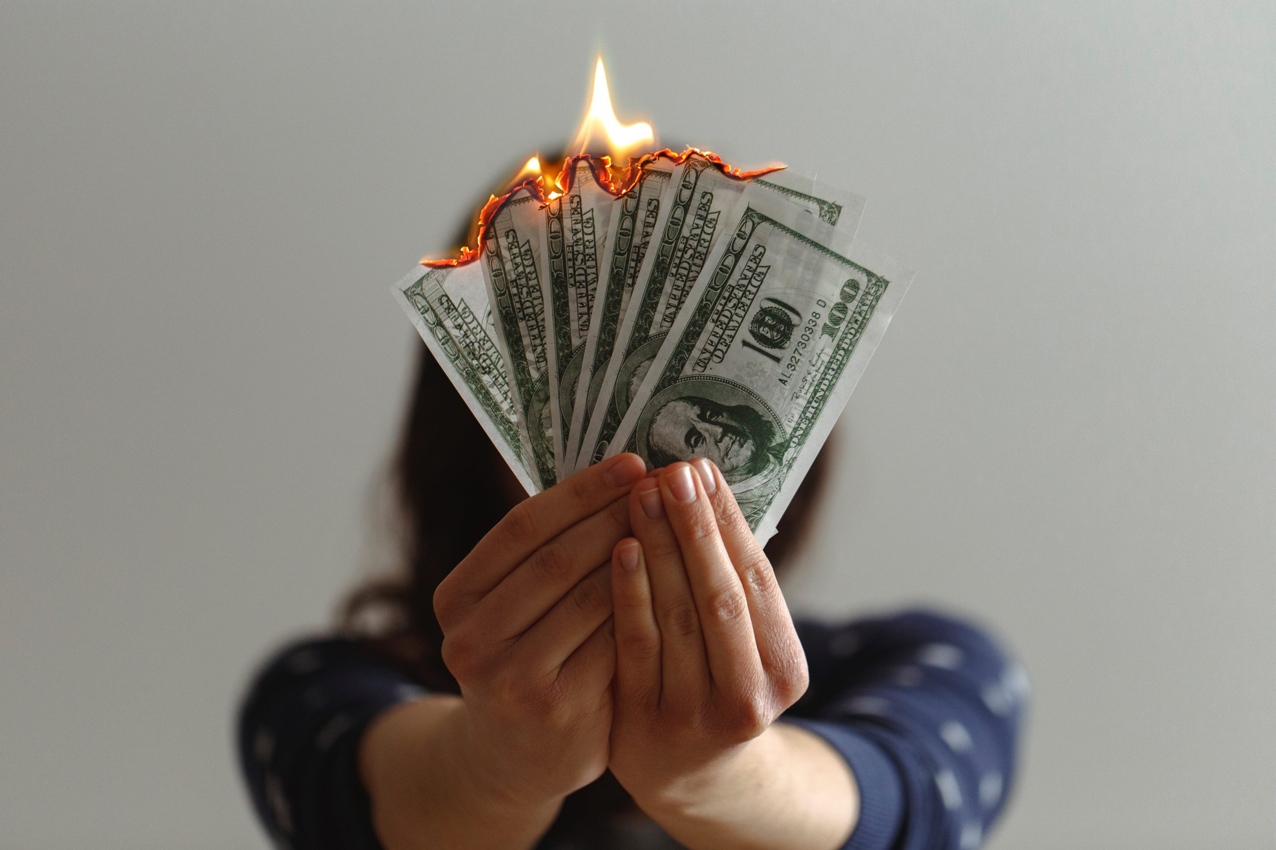 Woman holding a wad of burning money